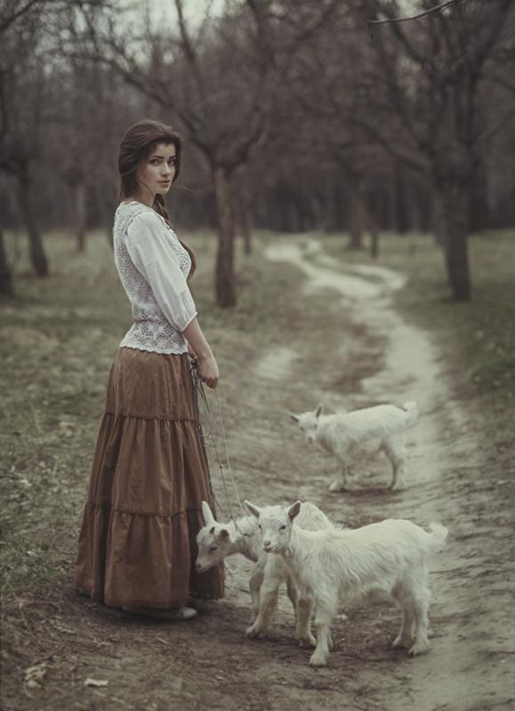 Klimatyczny portret fotograficzny dziewczyny wykonany w wiejskiej scenerii. Zdjęcie ma niezwykły ...