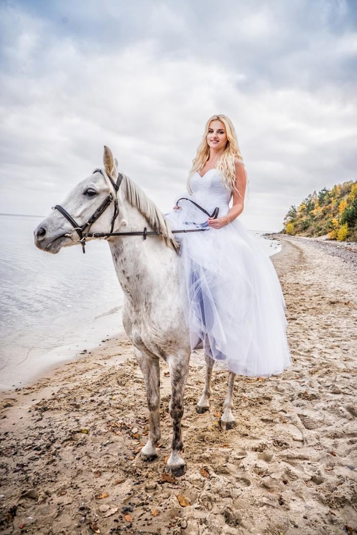 Panna Młoda na białym koniu. Piękna fotografia ślubna wykonana nad morzem.