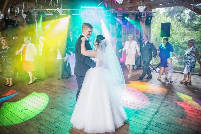 Pierwszy taniec Pary Młodej w otoczeniu gości, na udekorowanych światłem parkiecie w sali koło B ...