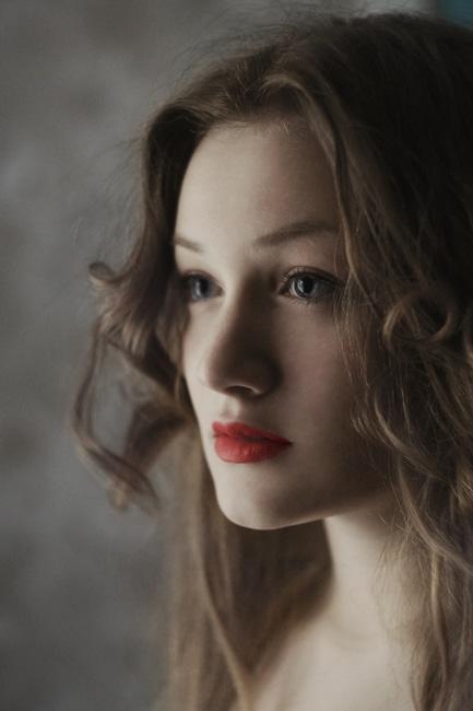 Subtelny portret kobiety z czerwonymi ustami i brązowymi włosami.